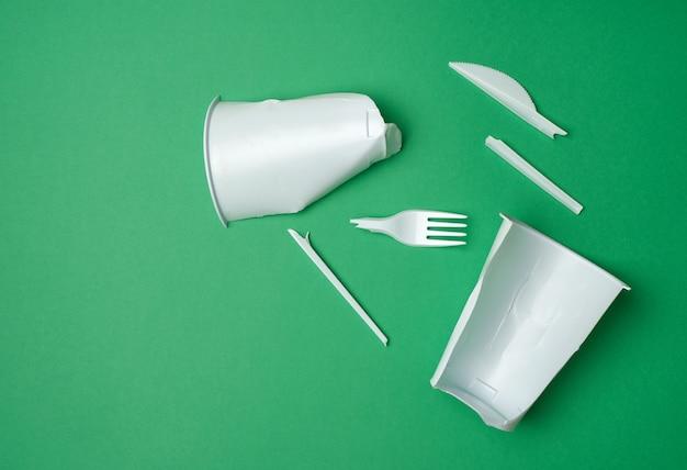 Resíduos de plástico não recicláveis de utensílios de mesa descartáveis, sobre um fundo verde, vista superior, plana