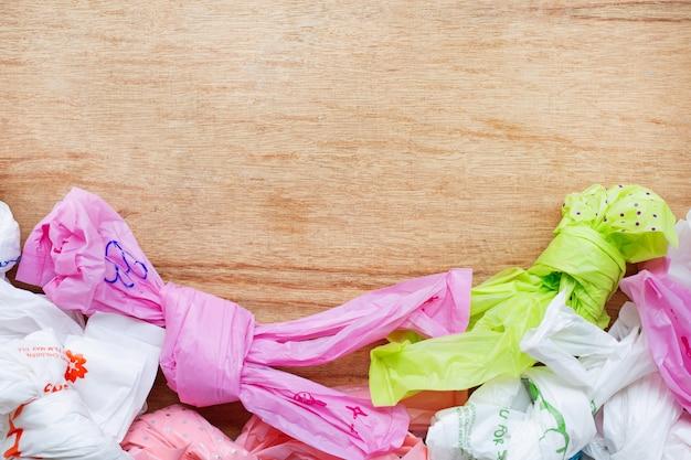 Resíduos de plástico, sacos de plástico no fundo de madeira.