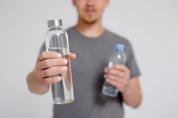Resíduos zero e conceito ecológico - jovem comparando água em vidro reutilizável e garrafa de plástico sobre um fundo cinza