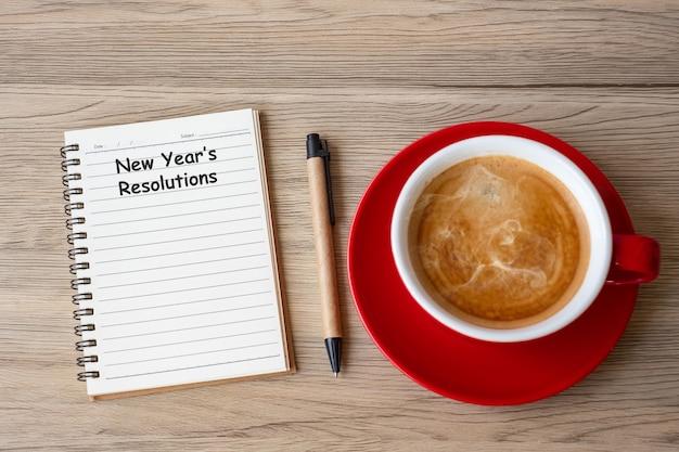 Resolução de ano novo com caderno, xícara de café preto e caneta na mesa de madeira. natal, feliz ano novo, metas, lista de tarefas, conceito de estratégia e plano