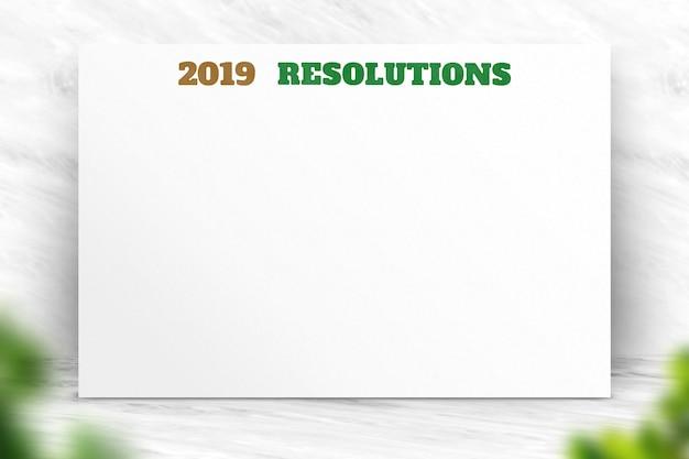 Resoluções de ano novo de 2019 no cartaz de papel com primeiro plano natural da folha do borrão