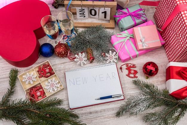 Resoluções de ano novo em bloco de notas com bolas coloridas e caixas de presente na mesa de madeira Foto Premium
