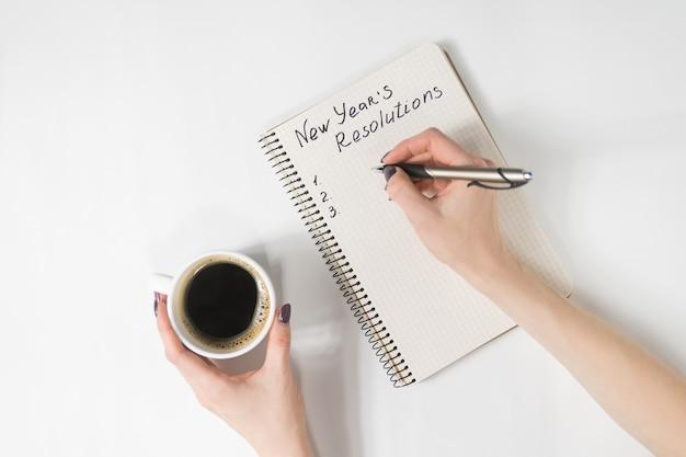 Resoluções de frase de ano novo no caderno, mão feminina com caneta e xícara de café