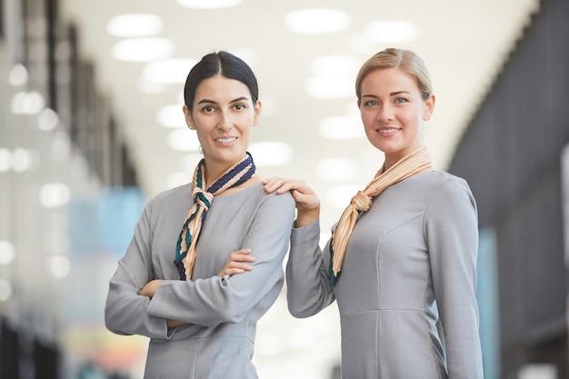 Resolva o retrato de dois elegantes comissários de bordo sorrindo enquanto posam no aeroporto