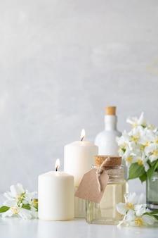 Resort spa em casa: óleo essencial de jasmim, velas e flores. conceito de spa.
