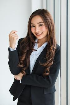 Respeitável empreendedor feminino asiático étnico em um terno preto elegante, em pé no escritório e olhando para a câmera com uma cara feliz amigável e positiva. fotografe com luz natural.