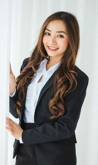 Respeitável empreendedor feminino asiático étnico em um terno preto elegante, em pé no escritório e olhando para a câmera com uma cara feliz amigável e positiva.