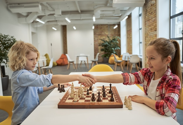 Respeite amiguinhos adoráveis, menino e menina caucasianos, apertando as mãos depois de jogar xadrez