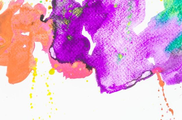 Respingo da aguarela colorida no fundo branco