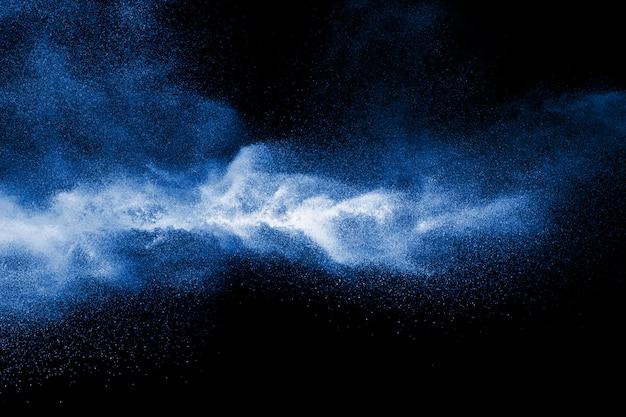Respingo da poeira azul do pó da cor no fundo preto.