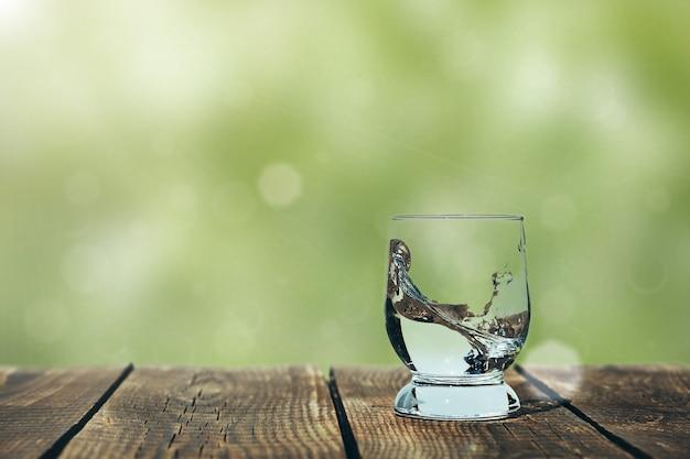 Respingo de água em um copo na madeira