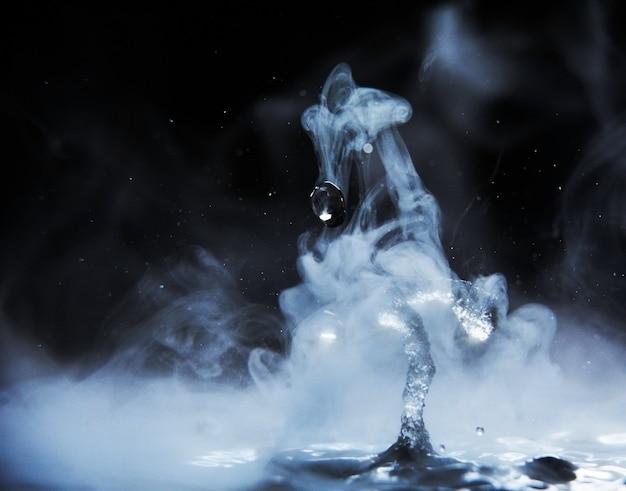 Respingo de água fervente com vapor em fundo preto