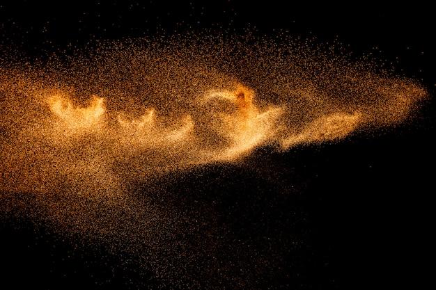 Respingo de areia de cor castanha. explosão de areia do rio seco isolada no fundo preto. nuvem de areia abstrata.