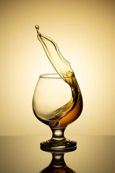Respingo de conhaque em vidro isolado em um fundo claro