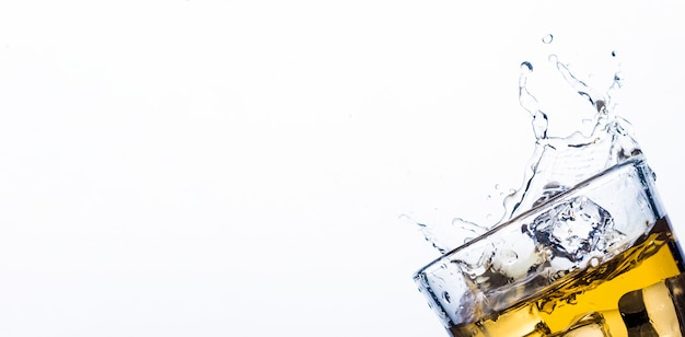 Respingo de uísque de cubos de gelo. conceito de bebidas alcoólicas com gelo, uísque ou conhaque, suco de maçã e bebidas refrigerantes. .