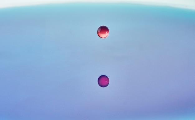 Respingos de água de cor de fundo abstrato, colisão de gotas coloridas caindo na água, arte conceitual com efeito abstrato.