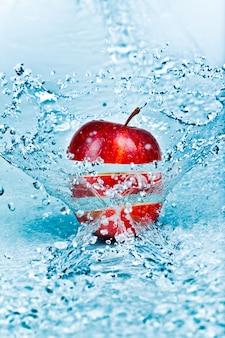 Respingos de água doce na maçã vermelha