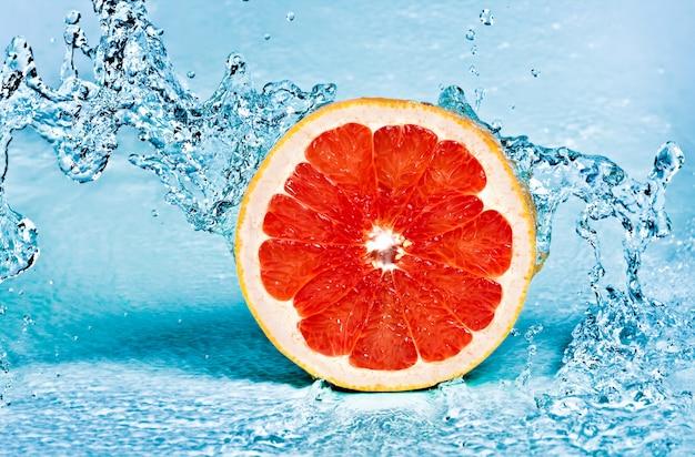 Respingos de água doce na toranja vermelha