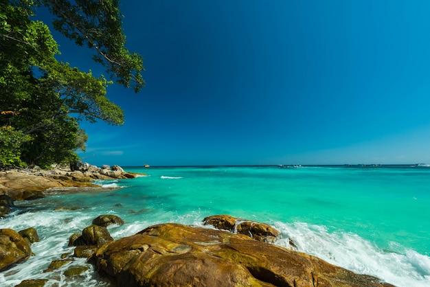 Respingos de água e as maravilhas da praia de pedra com céu azul