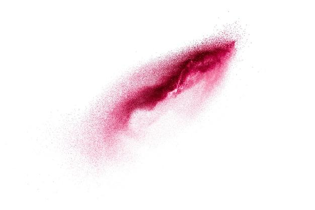 Respingos de areia de cor vermelha contra um fundo branco.