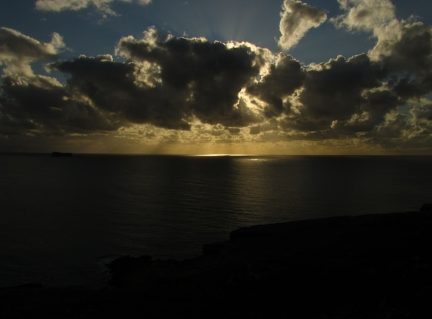 Respiração tomando o pôr do sol sobre o oceano com a ilhota de filfla em malta em um dia nublado