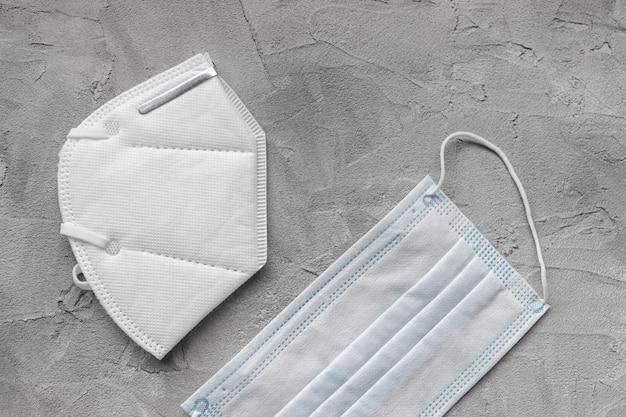 Respirador branco kn95 ffp2 e máscara médica em fundo cinza, copie o espaço. novas regras contra a mutação do coronavírus britânico e terceira onda de covid 19 na áustria, alemanha e outros países da ue