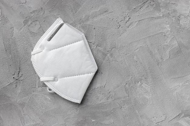 Respirador branco kn95 ou máscara ffp2 em fundo cinza, copie o espaço. novas regras contra a mutação do coronavírus britânico e terceira onda de covid 19 na áustria, alemanha e outros países no conceito da ue