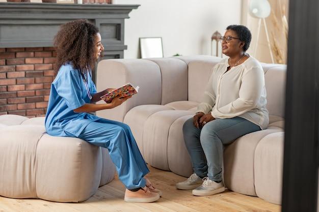 Respondendo a perguntas. senhora idosa se sentindo mal sentada no sofá respondendo às perguntas da enfermeira particular