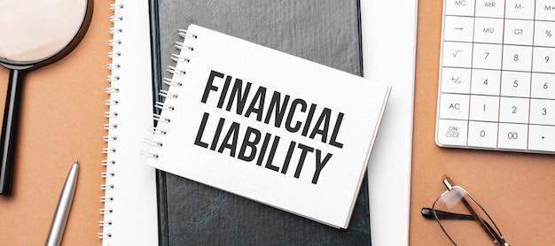 Responsabilidade financeira no bloco de notas e vários papéis comerciais na superfície marrom