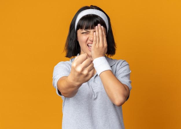 Ressentida e zangada, jovem fitness usando uma bandana mostrando o punho cobrindo o olho com a mão