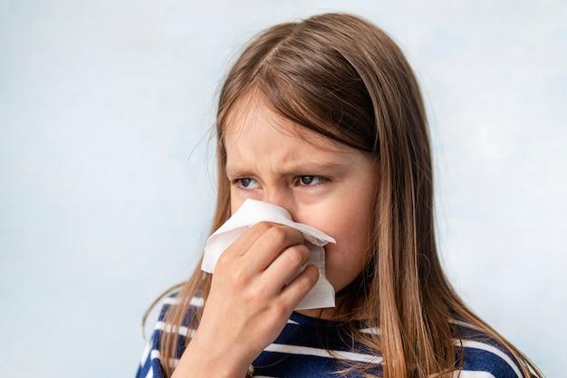 Ressentimento e lágrimas. a criança chora e enxuga o ranho com um guardanapo branco molhado. uma garota espirra em um pano sobre um fundo azul. uma criança doente está tossindo.