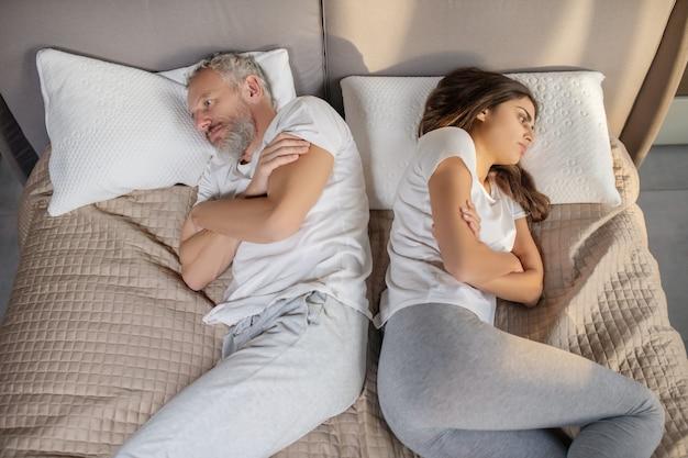 Ressentimento, família. homem triste de cabelos grisalhos e mulher de cabelos escuros deitados e virados em casa na cama