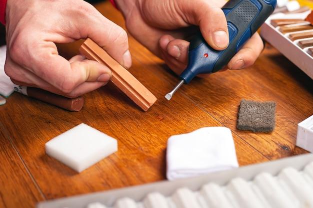 Restauração de laminados e parquetes. mestre fecha um close-up de ferramenta de reparo de superfície de madeira com arranhões ou lascas.