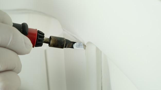 Restauração de superfícies de madeira, mestre sela o risco no close-up da porta branca.