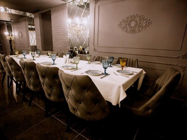 Restaurante chique pintado cinza com mesa de jantar vazia