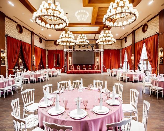 Restaurante com monitor pequeno palco, cortinas vermelhas, paredes de tijolo brancas cadeiras napoleão