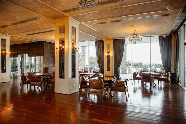 Restaurante com poltronas de couro e janelas francesas