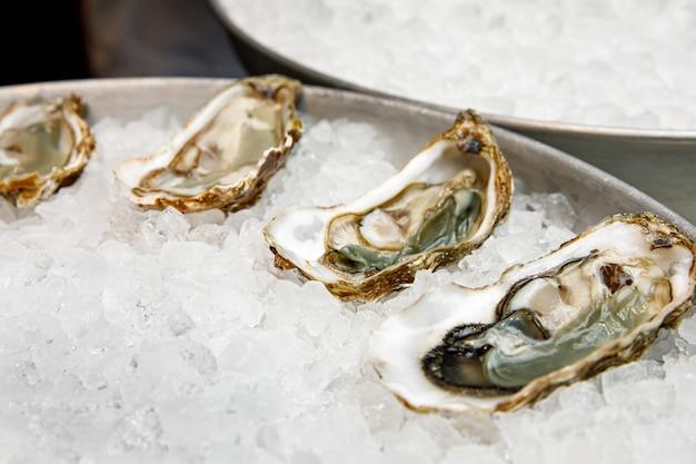 Restaurante de peixe. ostras cruas na bandeja com gelo.