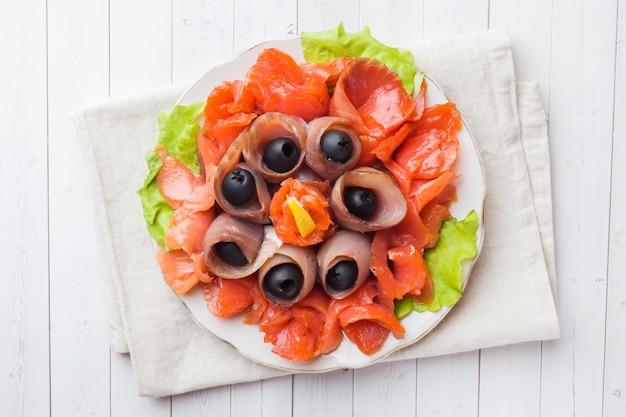 Restaurante gourmet que serve um prato de sal fumado, filetes de peixe branco cru e salmão.