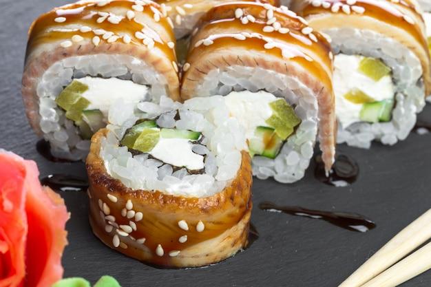 Restaurante japonês, rolo de sushi na placa de ardósia preta