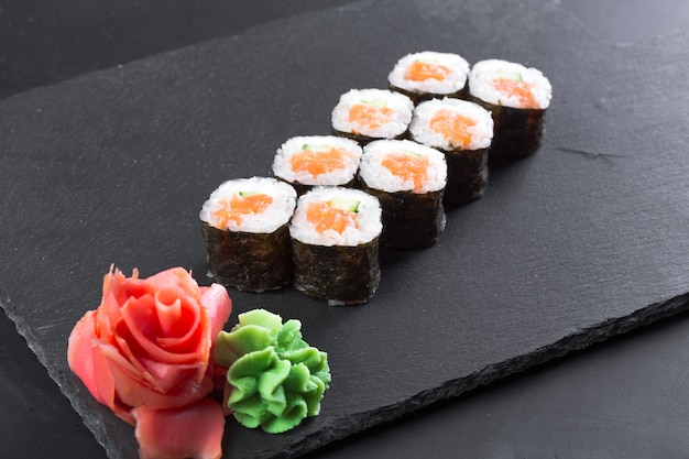 Restaurante japonês, rolo de sushi no prato de ardósia preta.