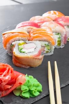Restaurante japonês, sushi roll na placa de ardósia preta.