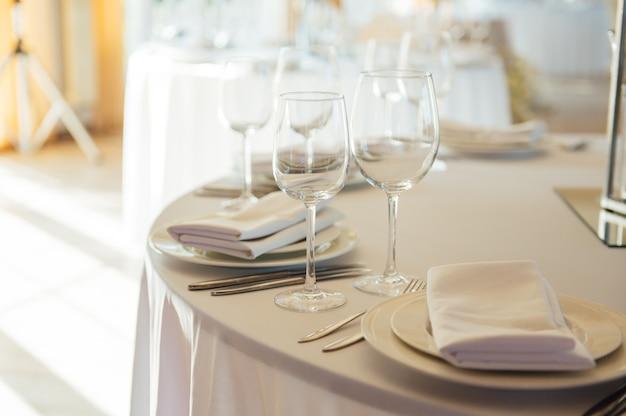 Restaurante luxuoso. interior luxuoso, mesas brancas, pratos e taças para convidados.