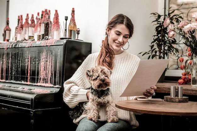 Restaurante que aceita cães mulher lendo o menu no café enquanto segura seu cachorro