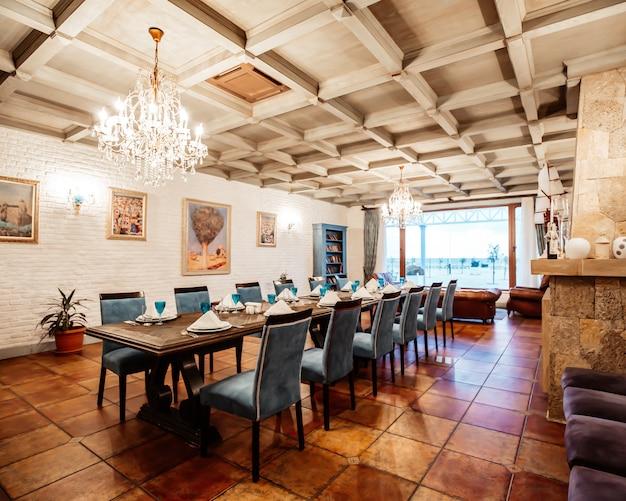 Restaurante sala privada com mesa para 12 cadeiras azuis, paredes de tijolos brancos, janela larga e pinturas