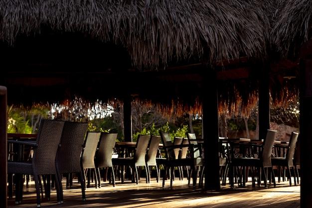 Restaurante tropical com mesas, iluminado por raios de sol, vazio.