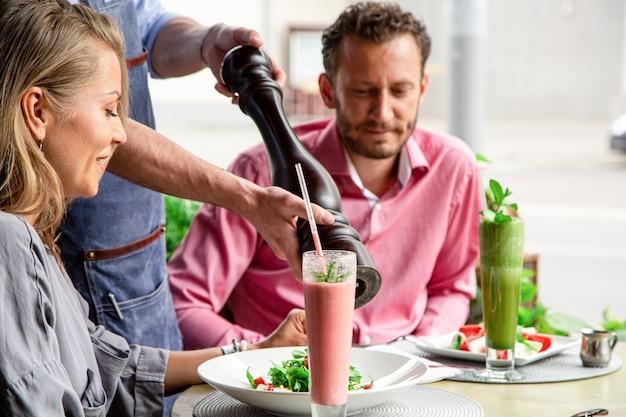 Restaurantes conceituais, serviço ao cliente. o garçom enche a salada com pimenta fresca.