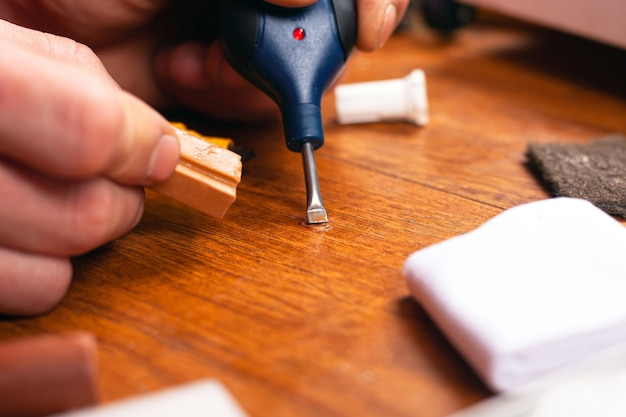Restauro de laminados e parquetes. mestre fecha um close-up de ferramenta de reparo de superfície de madeira arranhado ou lasca.