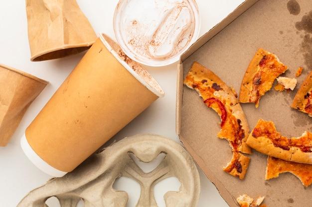 Restos de comida de pizza e copo descartável