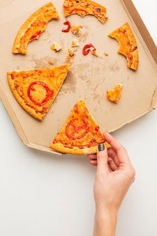 Restos de comida de pizza e pessoa pegando uma fatia